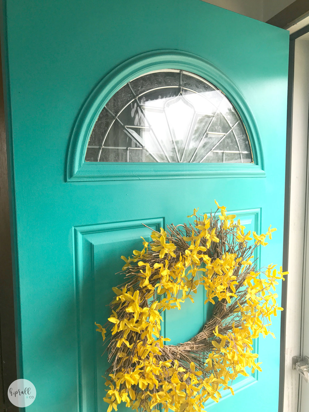 Bright yellow wreath hanging on a turquoise door via  H.Prall & Co.