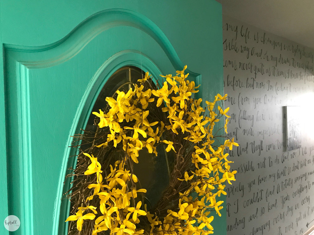 Yellow wreath on a turquoise door in front of a wall painted with song lyrics via  H.Prall & Co.