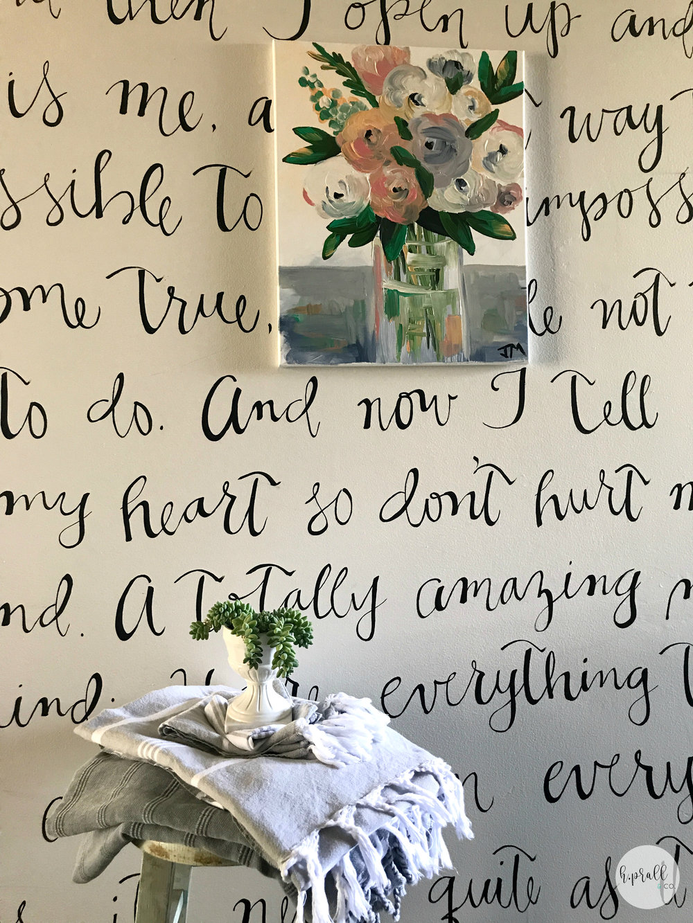 Folded up Turkish towels on a stool in front of a wall with hand painted song lyrics via  H.Prall & Co.