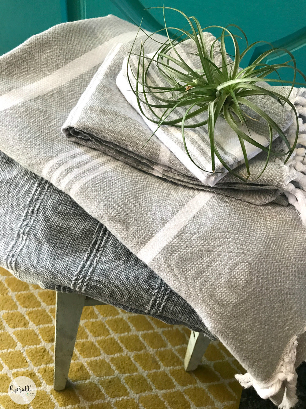 Gray and white striped Turkish towels folded up on top of a bar stool via  H.Prall & Co.
