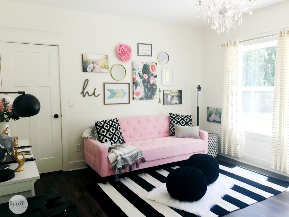 Feminine home office design by H.Prall & Co. featuring a pink couch, and a gallery wall with pops of pink for a bit of glamour! H.Prall & Co.