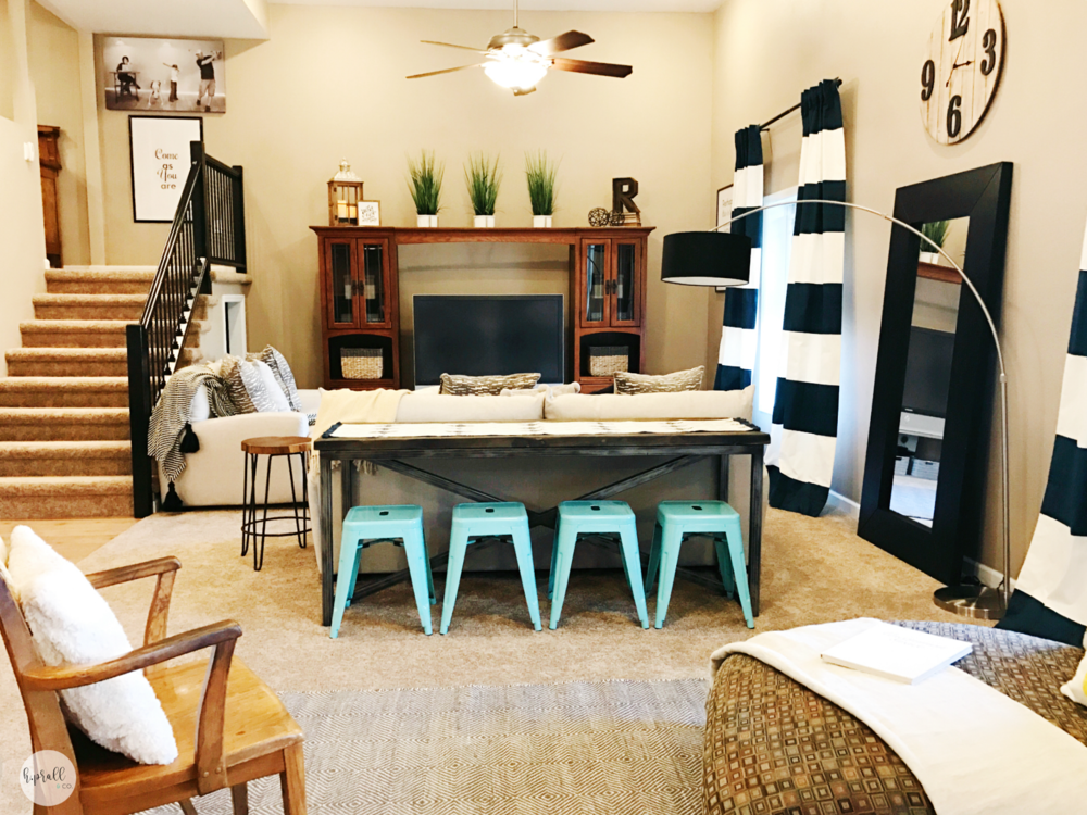 Living space with striped curtains, aqua barstools, and neutral furniture pieces. | hprallandco.com