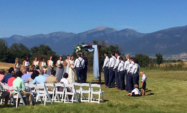 Exchanging vows in the meadow with a handmade arbor made from historic reclaimed wood.