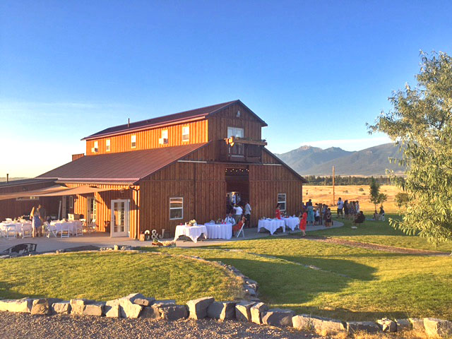 Guests out enjoying cornhole and pizza on the lawn in front of the barn.