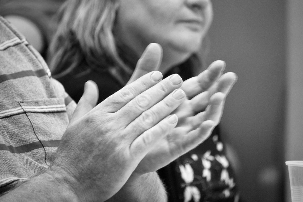 A close up of two mature hands about to clap. Part of a woman's face is out of focus in the background.