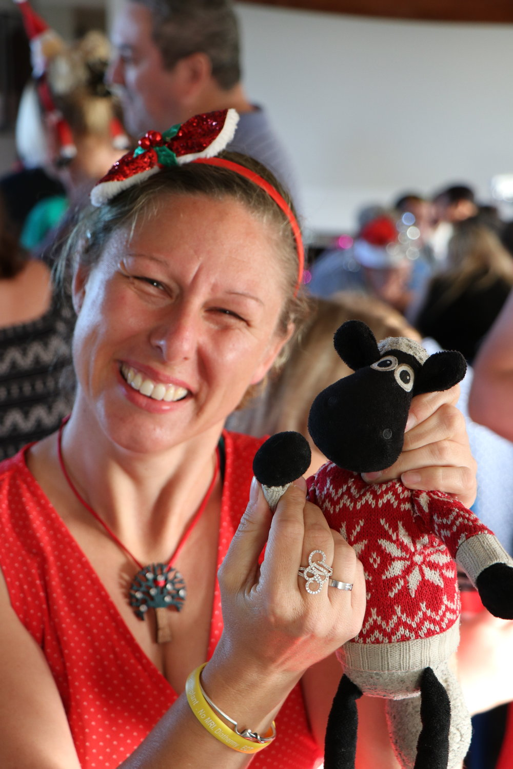 Photo of woman with toy sheep in her hands smiling.