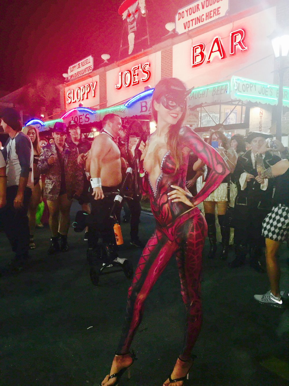 Alessandra Torre in red devil body paint on Duval Street at Fantasy Fest in Key West, in front of Sloppy Joes