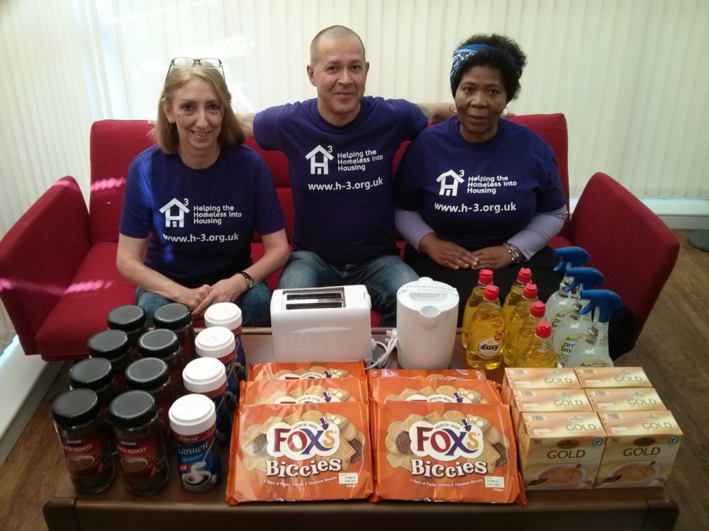 A Trustee, Project Worker, and Volunteer organising the Welcome Pack items