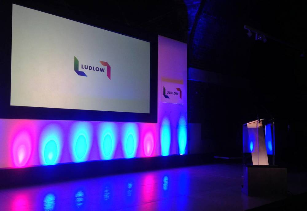 Branded conference stage set with lectern, lighting and AV in The Concert Room at The Lutyens Crypt.