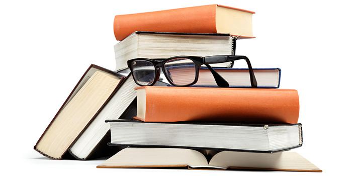 UNA IMAGEN DE UNOS LIBROS EN UNA BIBLIOTECA CON UNAS GAFAS JUSTO ENCIMA DE ESTOS LIBROS.  FLICKR