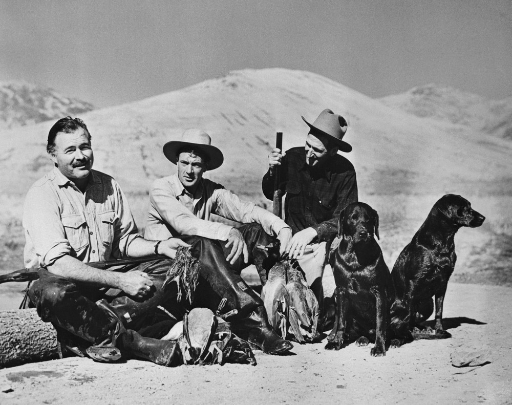 Author Ernest Hemingway, Idaho's most famous bird shooter, relaxes with screen star Gary Cooper, (C) and Taylor Williams (R) the sun Valley tour guide during a successful bird shoot.