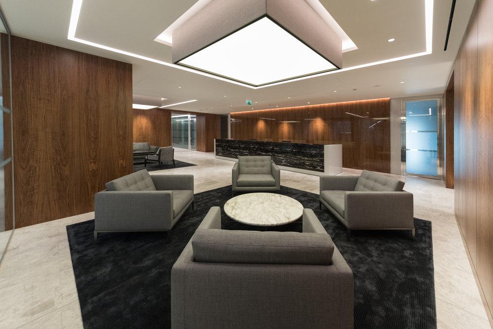 High gloss walnut veneer wall panels and 'silver portoro' stone desk to the main reception area
