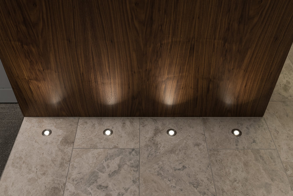 Walnut veneer portals showcased by floor lighting.