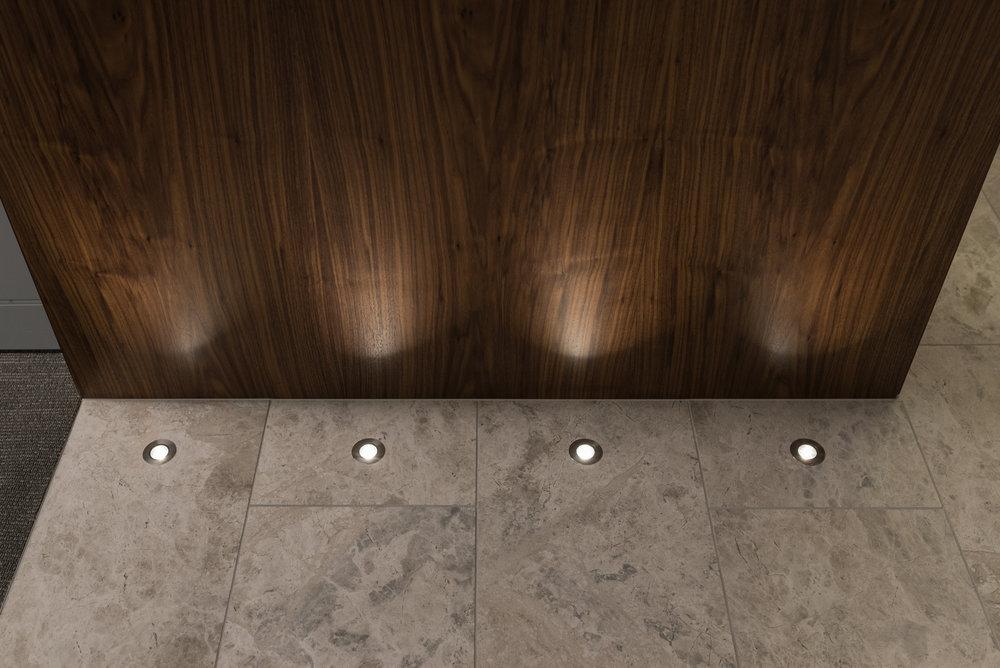 Walnut veneer portals showcased by floor lighting.