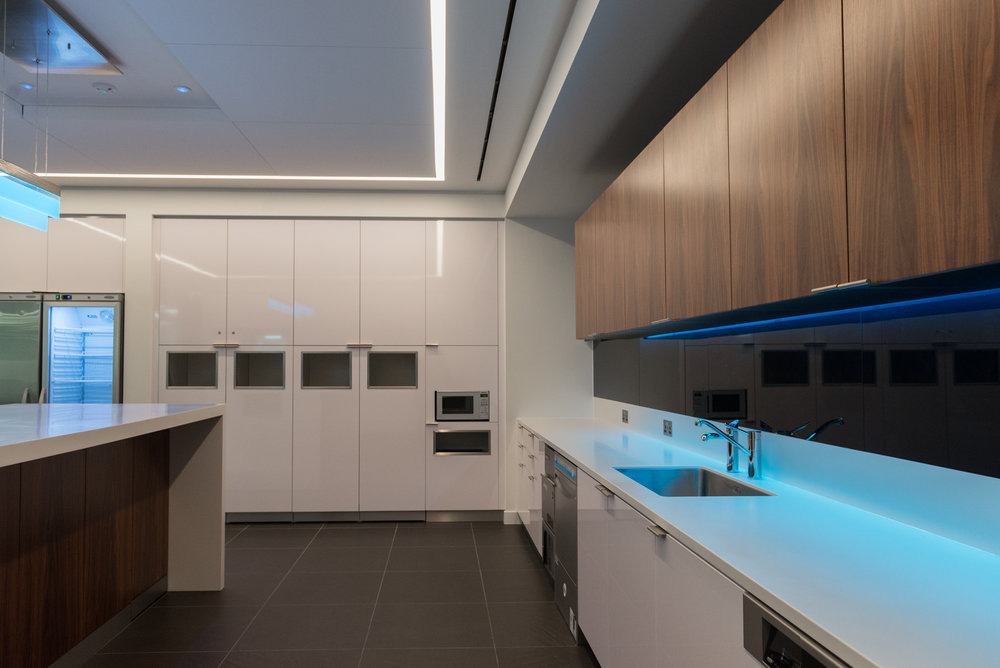 Walnut veneered wall units complement a Corian worktop and glass splashbacks in the main kitchen.