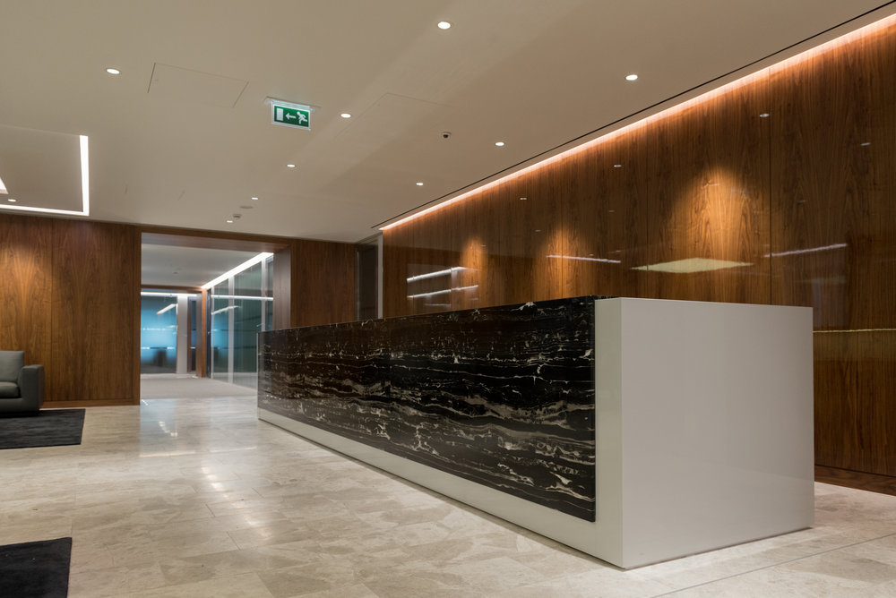 Our bespoke reception desk featuring stone and timber finished in high gloss pigmented lacquer.