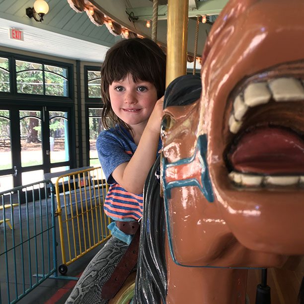 Arlo in snake skin pants riding a carved poplar horse on the antique carousel in Tilden Park.