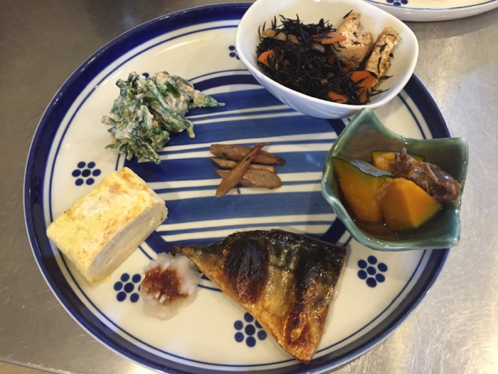 Roast burdock with black sesame, kabocha pumpkin simmered with dried dates, hijiki seaweed simmered with root vegetables and fried tofu, blanched spinach with creamy tofu sauce, tamagoyaki omelette, grilled salted mackerel and grated daikon radish
