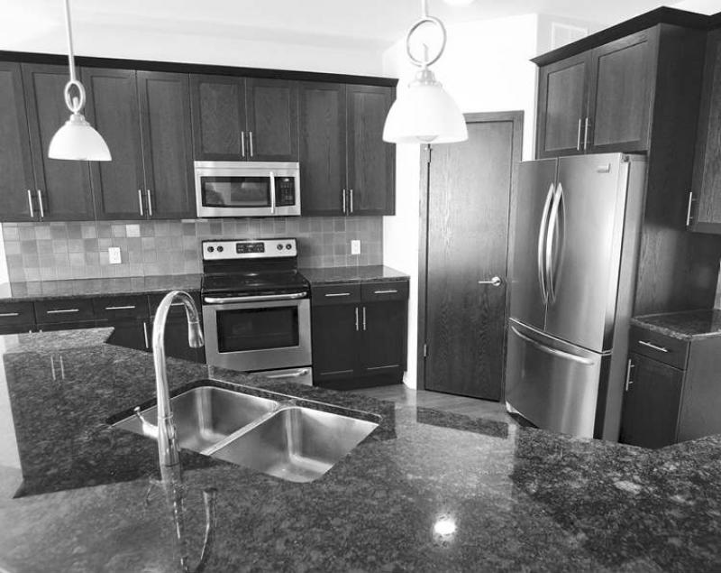 The kitchen features grey granite countertops and dark maple cabinets.