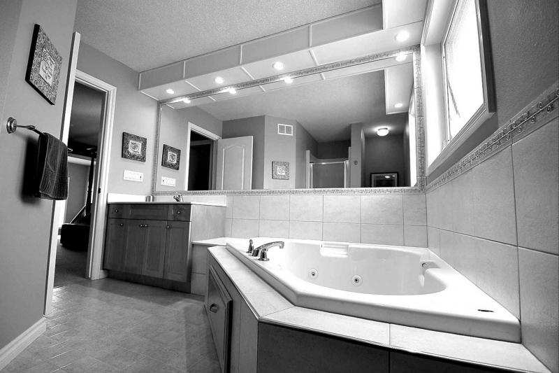 The spa-like ensuite is a bright, elegant space with a large window, tons of rich tile and a corner jetted tub to enjoy a soothing soak in.