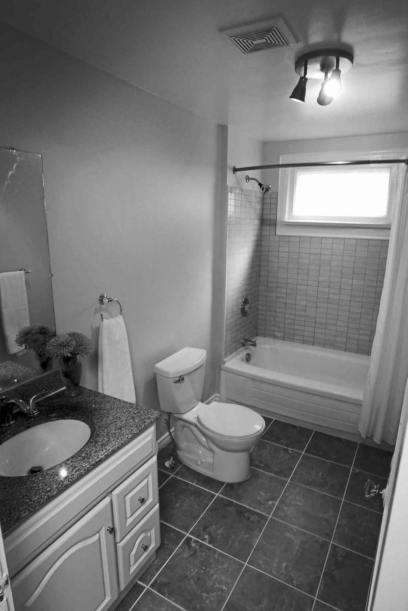 The master bathroom has been updated with grey tile flooring, white vanity and a tub with grey tile surround.