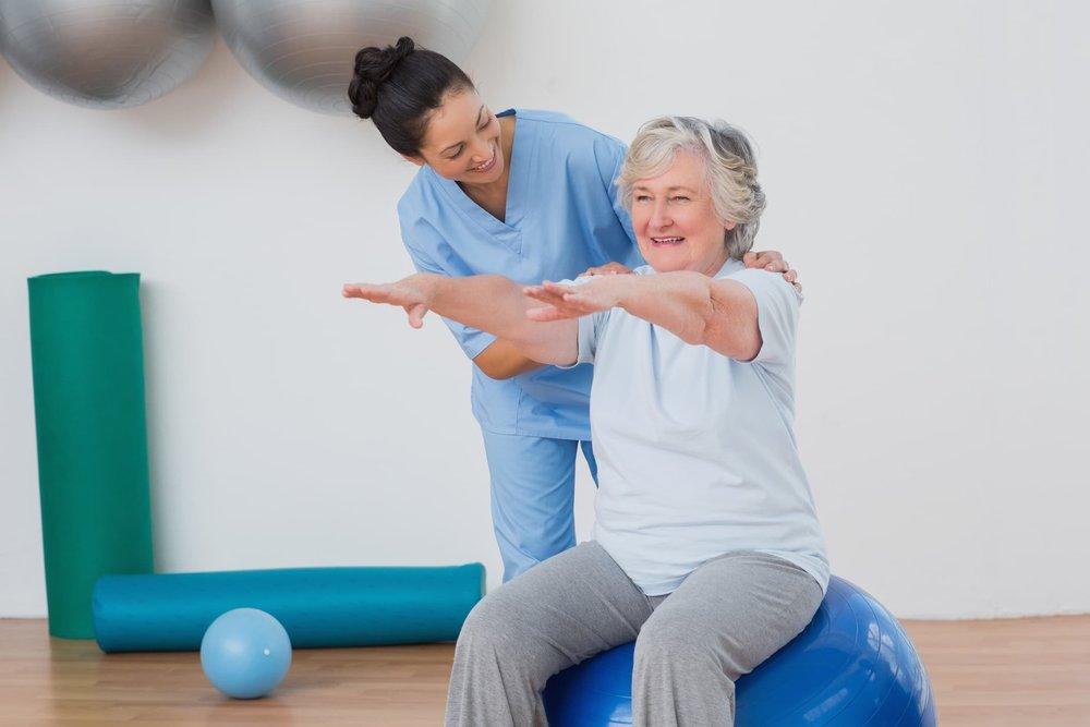 nurse-assisting-senior-in-exercises