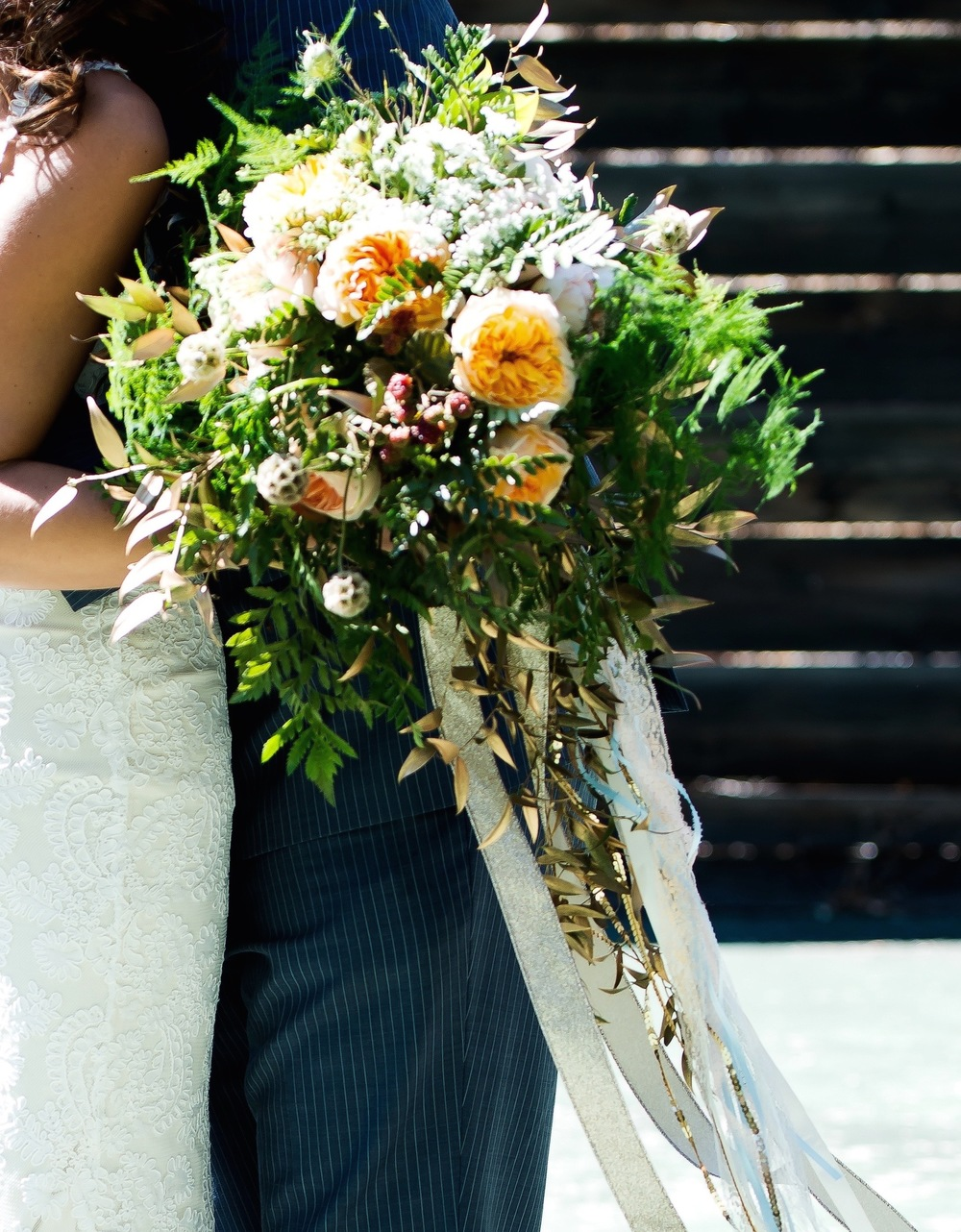 Romantic peach bridal bouquet with gold streamers