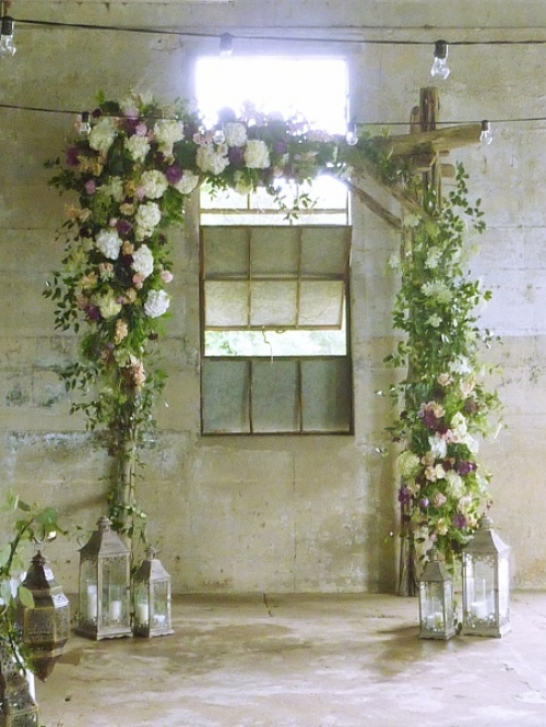 Arch with rustic treatment,  rough cut timbers , lushly adorned with vines and flowers. The lantern at the base anchor the posts that could appear bare.  Via www.noflowersnolife.xom