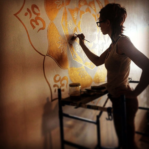 Caitlyn Saville painting gold Sacred Geometry Mediation Mural at Sin City Yoga Studio, located in Downtown Las Vegas, NV 2015.