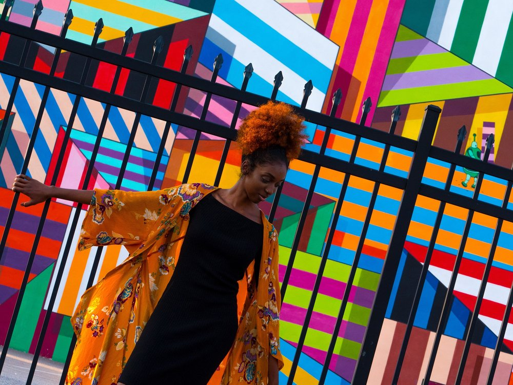 how to examine your inspirations. the image is of a black woman in front of a colorful wall.Create the highest, grandest vision possible for your life. because you become what you believe —Oprah Winfrey