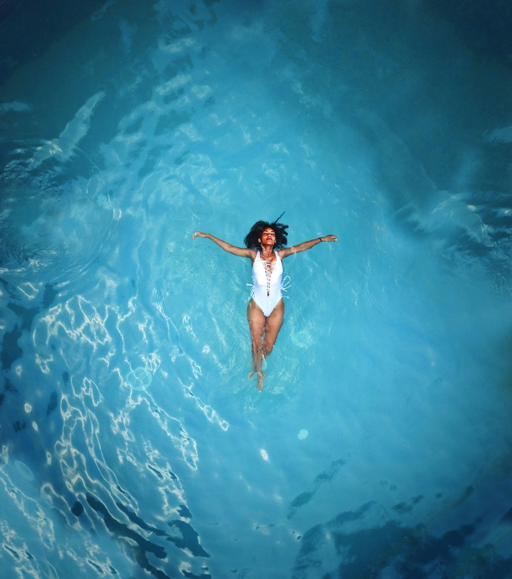woman in white monokini swimming in a body of water. Photo by  bruce mars