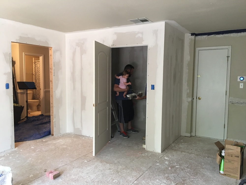 Me holding my baby and speaking to a contractor. You can see the corners and drywall ends have been leveled using the mud.