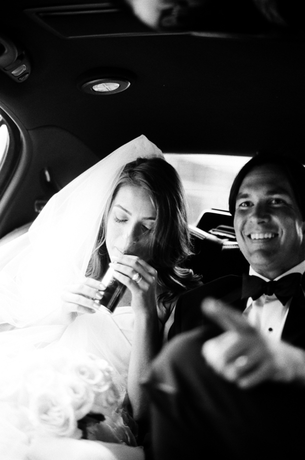 bride and groom in limo drinking champagne