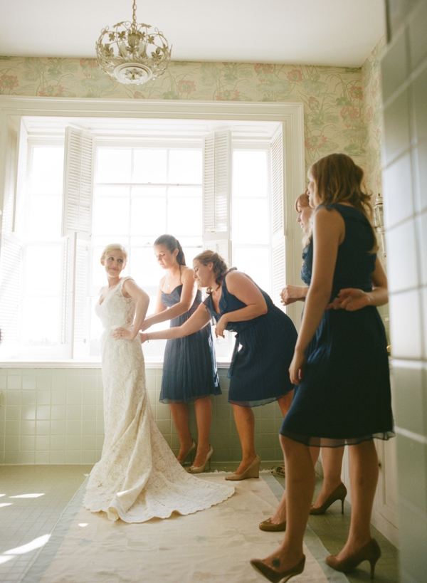bride getting dressed at home by bridesmaids