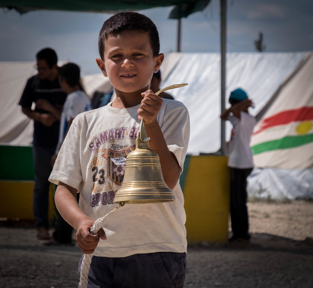 Khaled*, a student at the Lighthouse Relief school, sounds the bell to signal the start of classes in Katsikas refugee camp in northern Greece. (Lucas Bertoldo / Lighthouse Relief)