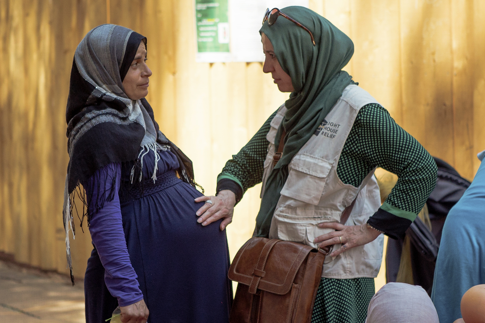 A volunteer community mediator asks a resident about her pregnancy (Arif Nurhakim / Lighthouse Relief)