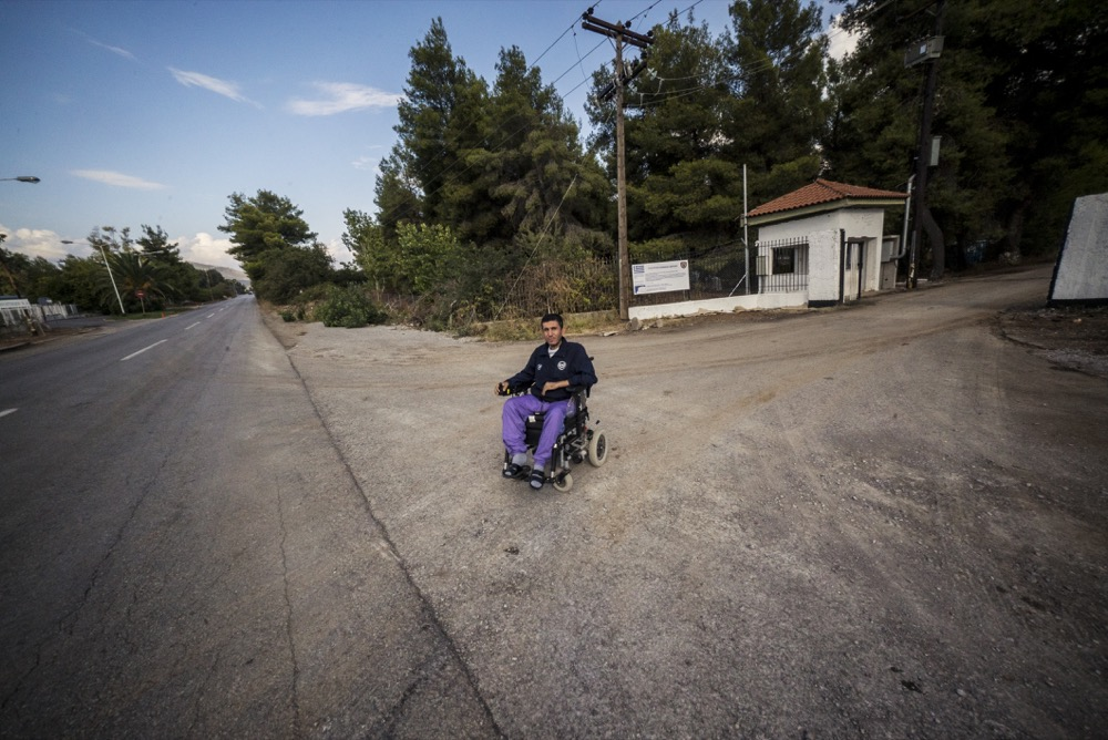 Alan at the entrance of Ritsona camp, and the long road to Chalkida. Photo: Tommy Chavannes/Lighthouse Relief