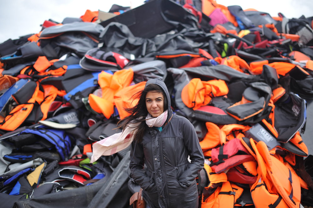 "Past Lighthouse Relief volunteer Marwa Bakabas stands in front of ""the life jacket graveyard"" in Lesvos, where hundreds of thousands of discarded life jackets used as refugees crossed the Aegean Sea have been collected. Photo: Anna Tascha Larsson/Lighthouse Relief"