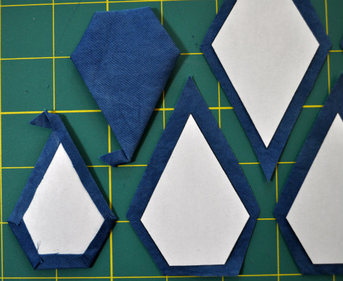 A few of the jewel shape paper pieces used in the outer border being wrapped and glue basted.