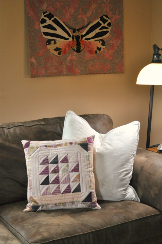 "This new pillow looks right at home in our Family Room with my art quilt   ""Self-Portrait""  ."