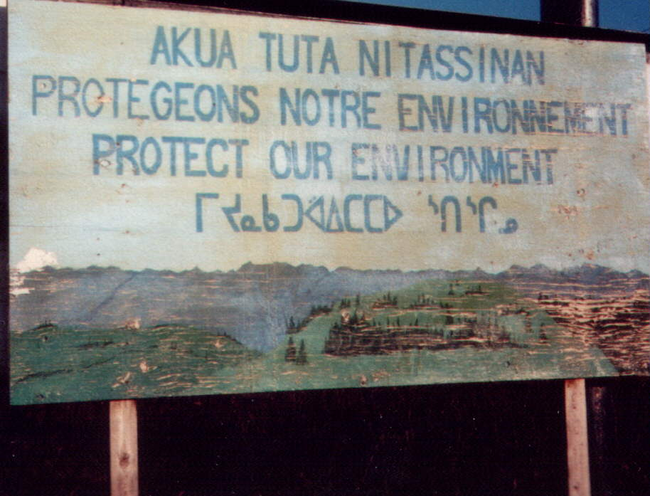 """Bill Jancewicz writes:  This sign, though it has disappeared in recent years, was for decades posted along the road between Schefferville and the mine site.  The top line is in Innu-aimun (Montagnais) and reads akua tuta nitassinan 'be careful with our (excl) land'.  The second line is French, Protegeons notre environnement 'let us protect our environment' and the third line is English.  The bottom line is in Naskapi and readsᒥᔪᓇᑲᑐᐛᐃᑕᑕᐅᔅᑎᔅᒋᓄ miyunakatuwaaiitaataau stischinuw 'let us care for our (incl) land'.  Even though this sign was painted and transcribed in Naskapi prior to the orthographic standardization described in detail in other sections of this thesis, there is enough detail to show a significant difference in the grammatical structure of the word 'land' for Naskapi and Montagnais.  In Montagnais, the word assi 'land' is inflected with a prefix and suffix that indicates to the reader that the land thus referred to is """"ours,—but not yours."""" The word nit‑assi‑naan 'our land' is first person plural exclusive .  However, in Naskapi, the word aschiy 'land' is inflected with a different prefix and suffix that indicates to the reader that the land thus referred to is """"ours,—yours and mine together."""" The Naskapi word (here spelled phonologically) chit‑aschi‑nuw 'our land' is second person plural inclusive .  For the Naskapi,there was a conscious choice of the different grammatical structure used for the """"same"""" lexical item""""land""""reveals something of the unique Naskapi speaker attitude towards the land.    - Adapted from his thesis, """"Grammar Enhanced Biliteracy: Naskapi Language Structures for Facilitating Reading in Naskapi."""" Master's thesis, University of North Dakota, 2013. https://arts-sciences.und.edu/academics/summer-institute-of-linguistics/theses/_files/docs/2013-jancewicz-william.pdf"""