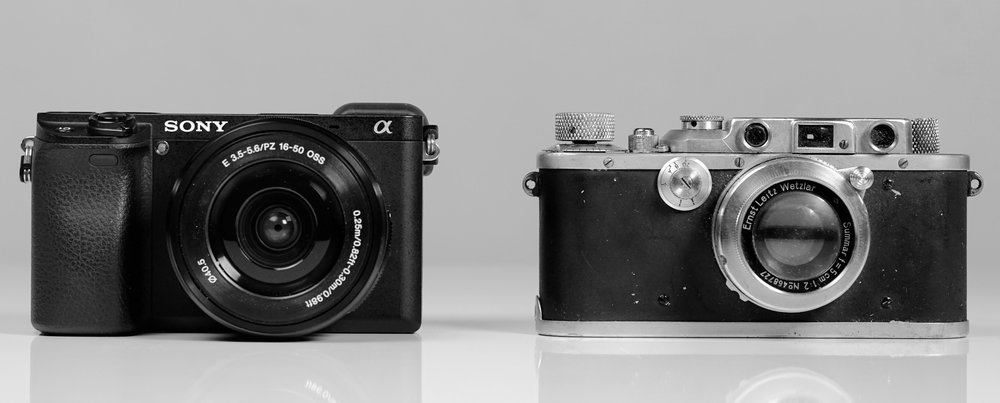That's my mother's Leica IIIa on the right, bought second-hand from Bauhaus trained photographer Hilde Hubbuch, similar to the one used by Henri Cartier-Bresson.  This is the camera that introduced me to photography. On the left, my Sony a6300 with kit lens for size comparison.