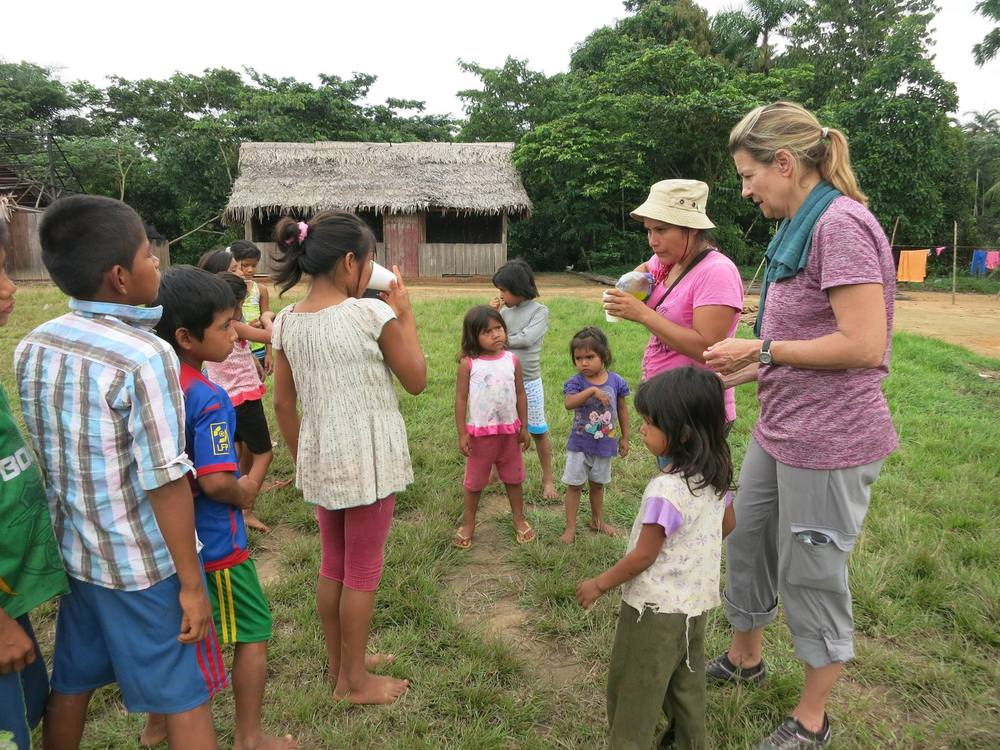 "Melony and Interpreter ""Dorcas"" giving the kids a drink break after playing bible games"