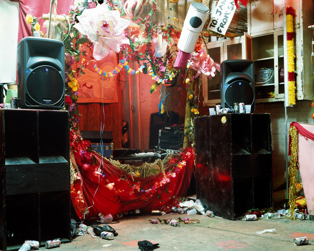 These images were made in loft spaces in Brooklyn after huge parties and art events.  I revel in the lushness of what is left behind in these makeshift spaces that are true labors of love by their creators, and the little mysteries that they reveal.  There is a tension created between happiness and sadness: an elaborately decorated DJ booth, crushed empty cups strewn about the floor, and large, silent, black speakers amongst traces of a celebration, with no celebration to be seen.  It is the after and the in-between that interest me most and It is here that the conversation happens for me.