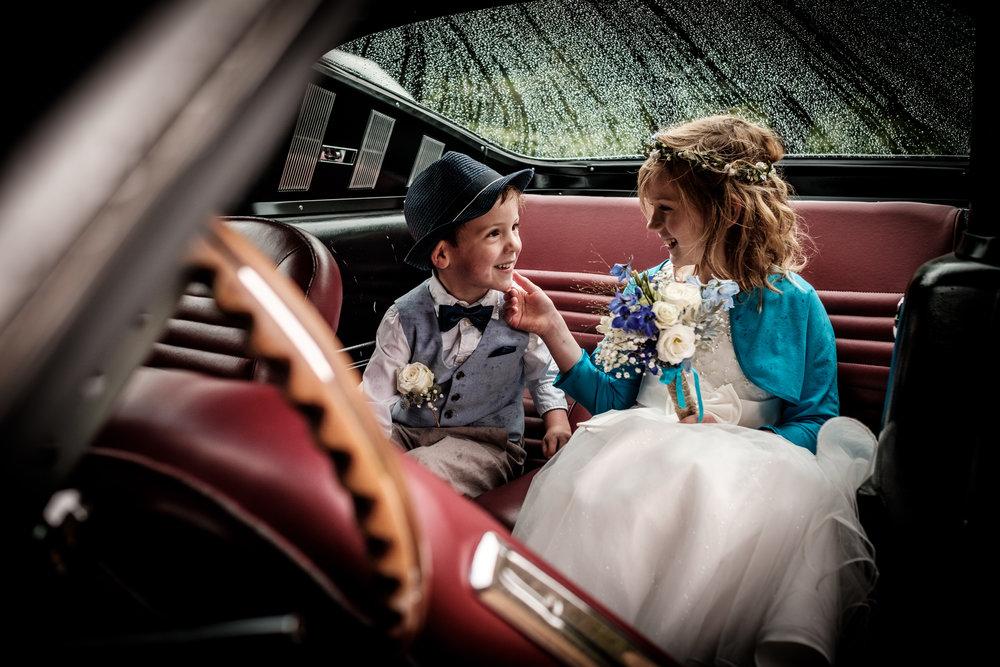 Schattige bruidskindjes in een prachtige sfeervolle bruidsauto.