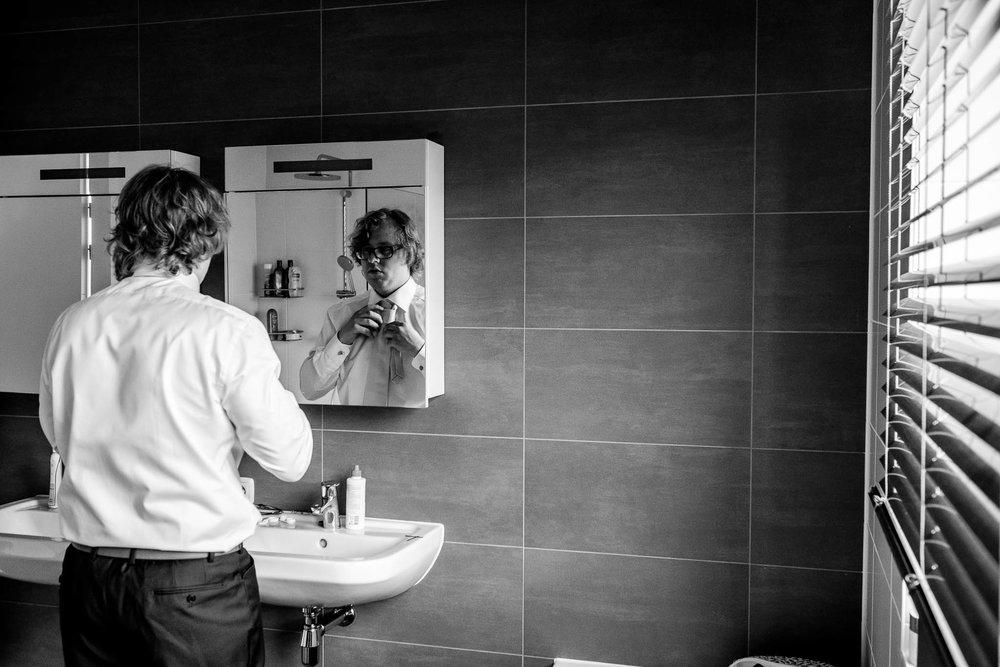 Bruidegom staat in de badkamer