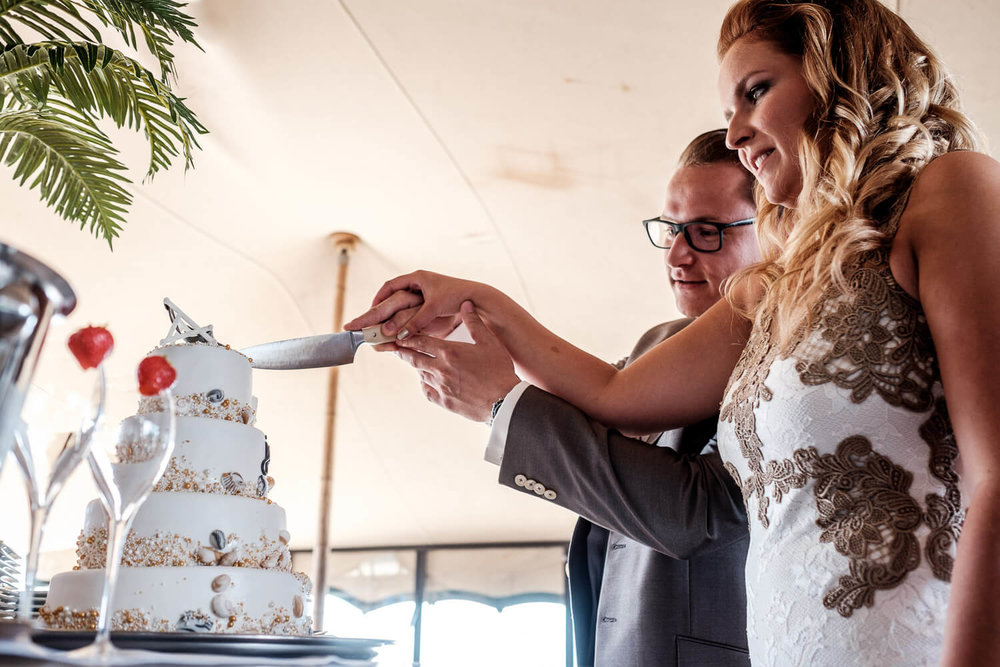 Beach wedding Geluk taart aansnijden