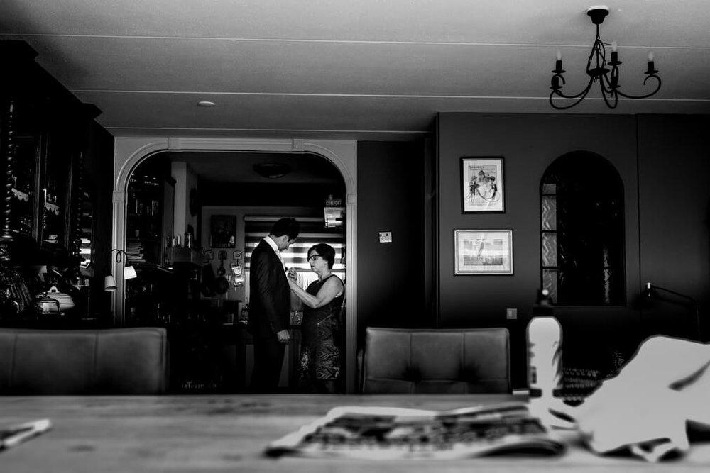 Journalistieke trouwfotografie in Leerdam. Bruidegom maakt zich klaar in woonkamer. Mitzy fotografeerde dit journalistiek, ongedwongen en ongeposeerd. Leerdam. Zuid-Holland trouwfotografie.