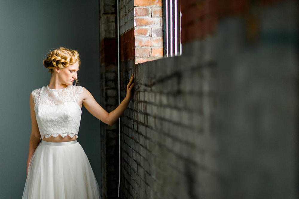 Photo of a bride against an exposed brick wall
