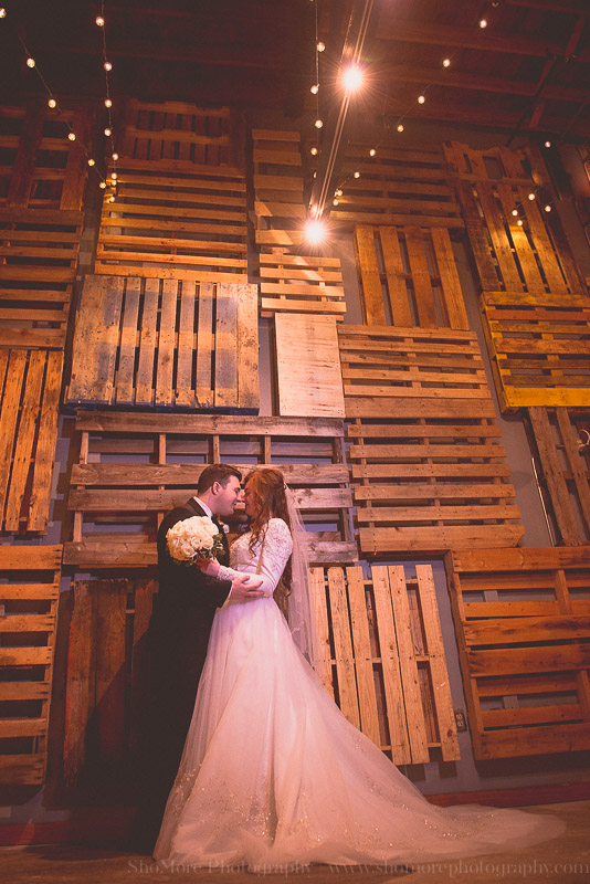 This is a picture of a bride and groom in front of our breathtaking pallet wall.